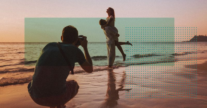 Freelancer taking a photo of a couple on the beach